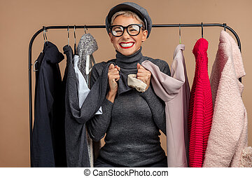 positive cheerful gorgeous female customer is among outfit