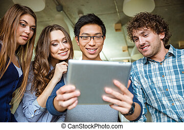 Positive cheerful happy friends using tablet