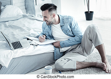 Positive cheerful man holding a notebook
