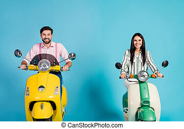 Positive cheerful two lovely bikers man woman drive their motor bike wear striped shirt pink isolated over blue color background