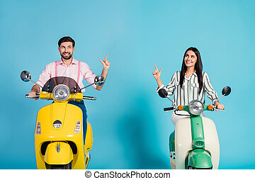Positive cheerful two people bikers ride fast speed electric scooter follow way to journey point index finger copyspace wear striped pink shirt isolated over blue color background