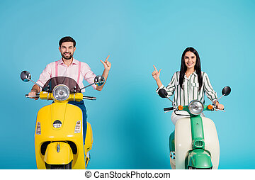 Positive cheerful two people driver drive yellow green motor bike follow way to resort point index finger copyspace wear formalwear shirt isolated over blue color background
