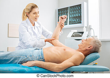 Positive cheerful woman holding her patients arm