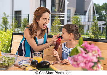 Positive cheerful woman putting ketchup on her daughters nose