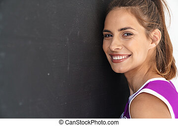 Positive cheerleader woman posing near black and white wall