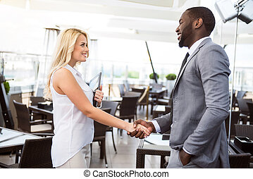 Positive colleagues shaking hands