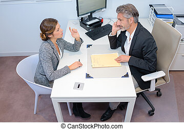 positive conversation between businessman and potential client in office