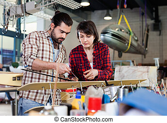 Positive couple enjoying their hobbies - modeling light airplanes in aircraft hangar