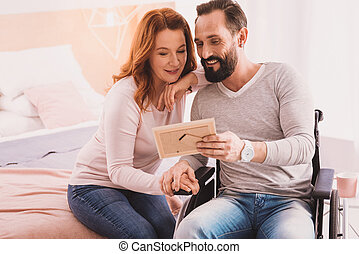 Positive couple lookign at a photo frame