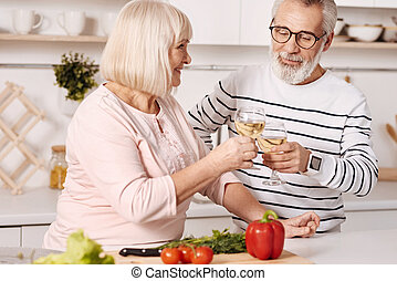 Positive couple of pensioners enjoying champagne in the kitchen