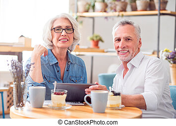 Positive couple resting in the cafe