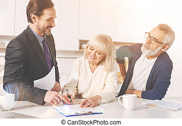 Positive couple signing papers with insurance agent