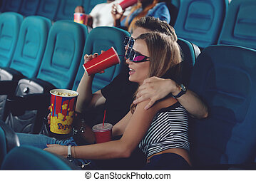 Positive couple spending free time in cinema.