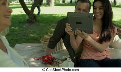 Positive couple taking photos of a senior woman