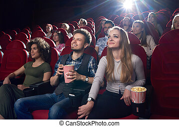 Positive couple watching funny movie at cinema and eating popcorn.