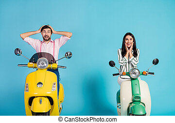 Positive crazy energetic two bikers man woman drive power motor bikes look incredible discount ads impressed touch hands cheeks face scream isolated over blue color background
