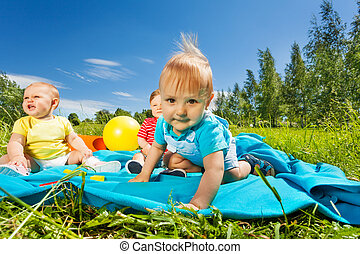 Positive cute toddlers sit on blanket in field