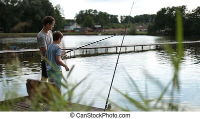 Positive dad and son with rod angling at pond - Positive dad...