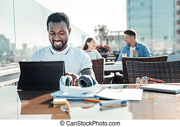 Positive delighted Afro-American male looking at his tablet