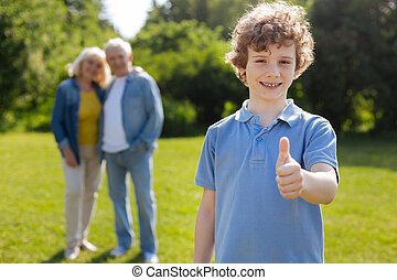 Positive delighted boy with curly hair standing on the foreground