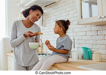 Positive delighted brunette woman giving sandwich to child