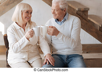 Positive delighted couple clinking cups