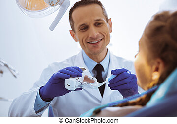 Positive delighted dentist teaching his patient