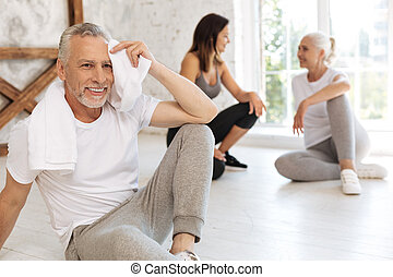 Positive delighted elderly man whipping his forehead