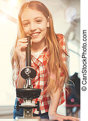Positive delighted girl posing with microscope