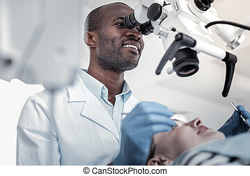 Positive delighted international dentist examining his patient