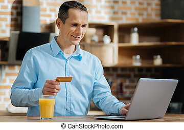 Positive delighted man doing online shopping