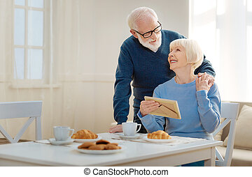 Positive delighted man embracing his wife
