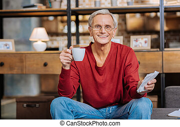 Positive delighted man enjoying his coffee