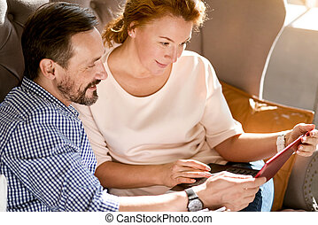 Positive delighted middle aged couple relaxing at home