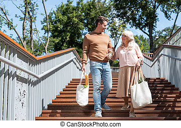 Shopping day. Charming retirement going downwards on stairs and communicating with young male person