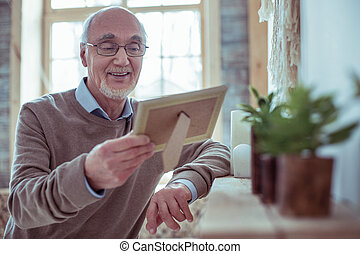 Positive delighted retirement looking at family photo