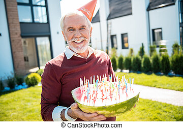 Positive delighted senior male person poising on camera