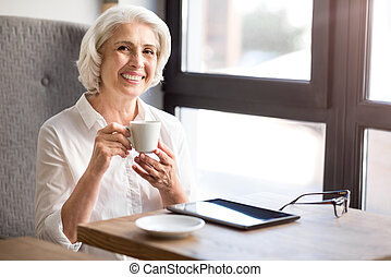 Positive delighted senior woman working with papers