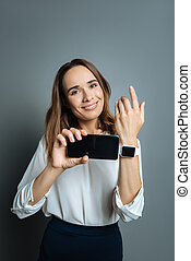 Positive delighted woman holding her smartphone