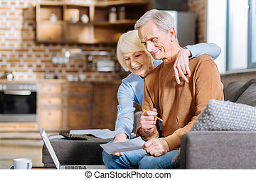 Positive delighted woman hugging her husband