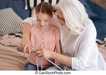 Positive delighted woman knitting with her granddaughter