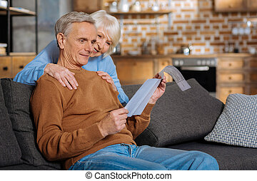Positive delighted woman putting hands on her husband shoulders
