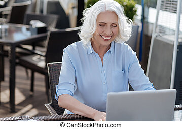 Positive delighted woman working with laptop