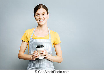 Positive delighted young woman going to drink coffee