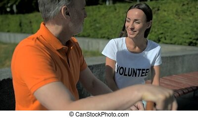 Positive devoted volunteer talking with the senior man -...