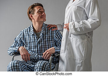 Positive disabled man in carriage supported by hospital worker