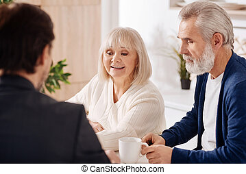 Positive elderly couple having conversation with advisor at home