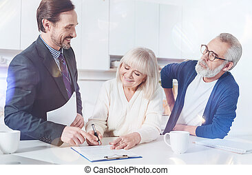 Positive elderly couple meeting with their insurance agent