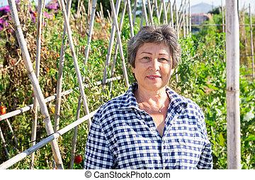 Positive elderly female gardener in backyard garden