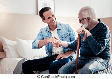 Positive elderly man greeting his son